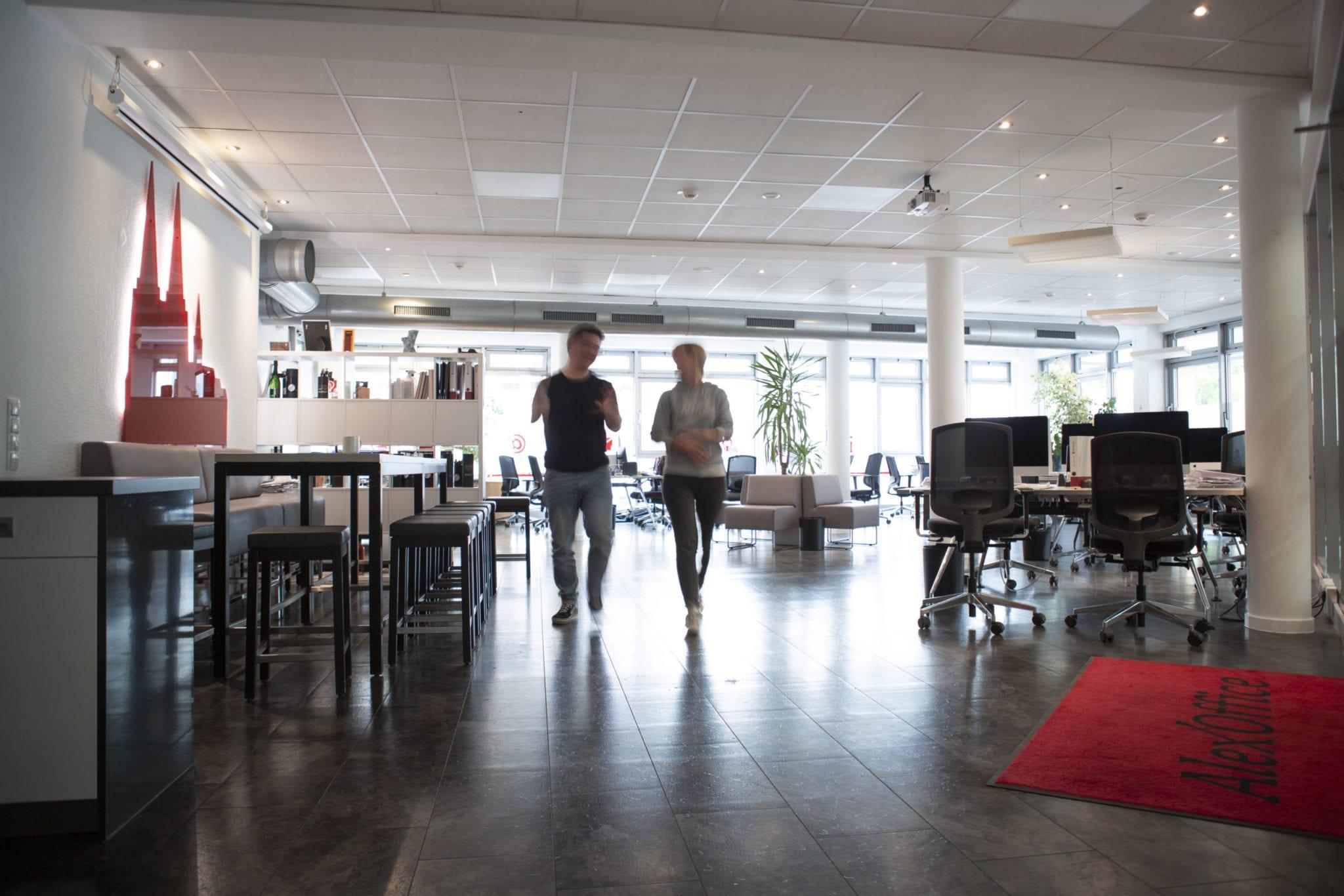 Zwei Menschen in einem Büro, die sich beim Gehen unterhalten