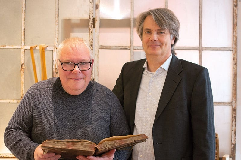 Zwei Männer, von denen einer ein Buch in der Hand hält