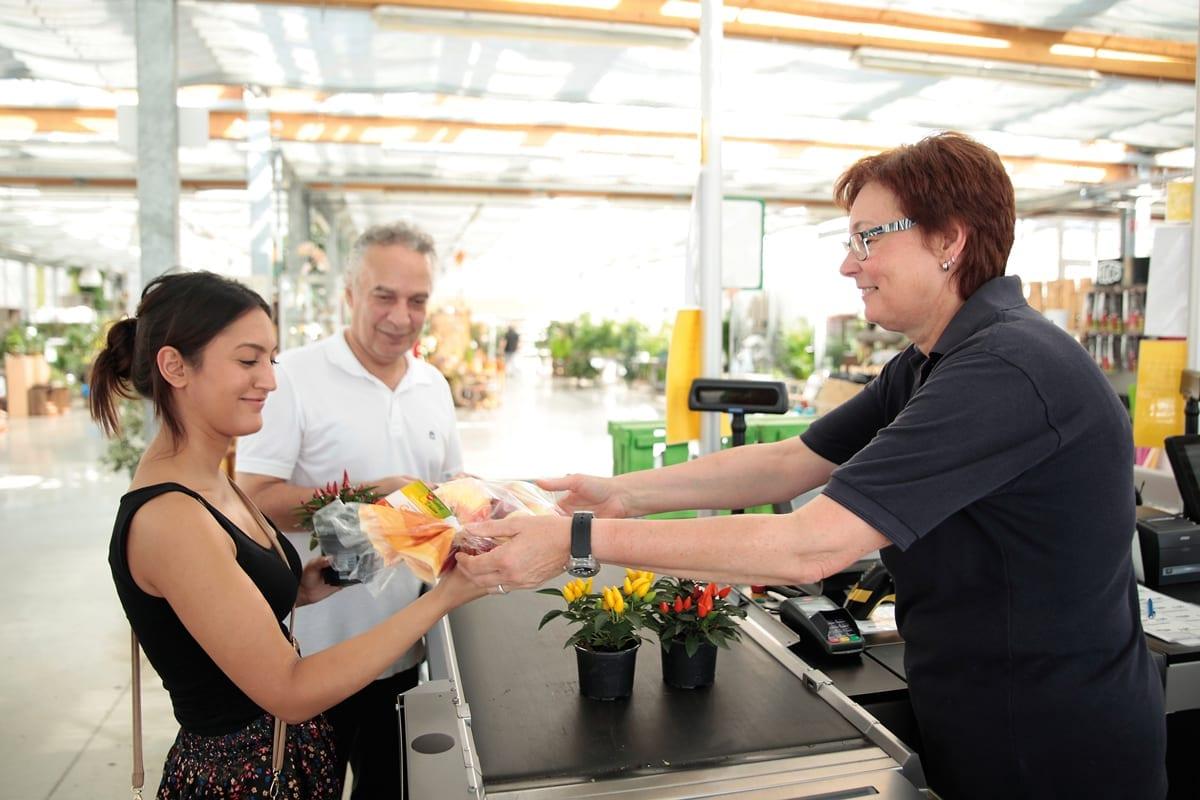 Eine Frau, die an der Kasse Pflanzen kauft