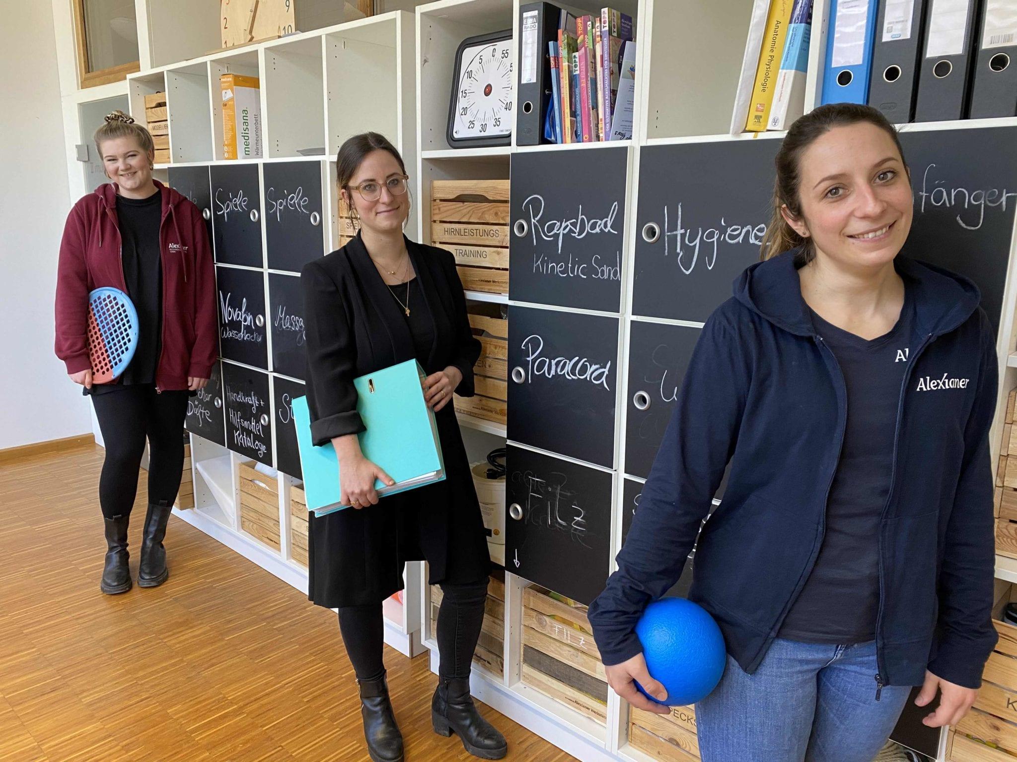 Drei Mitarbeiterinnnen stehen in der Praxis vor einer Materialwand.