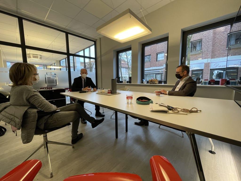 Menschen im Gespräch an einem Tisch im Besprechungsraum.