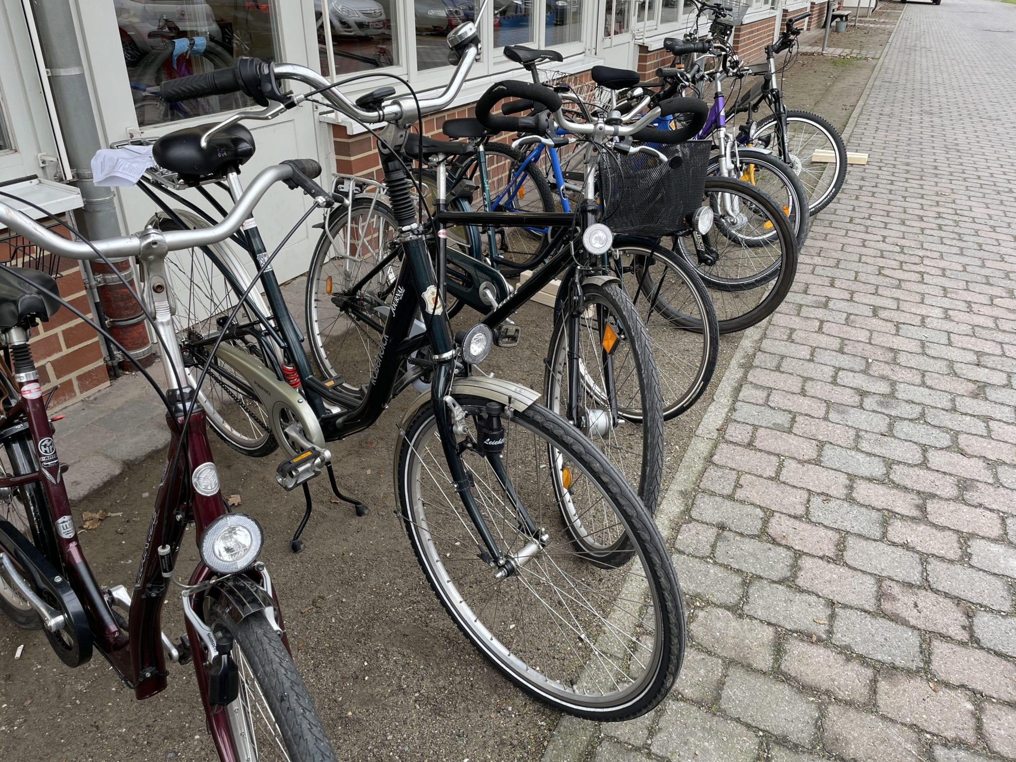 Mehrere gebrauchte Fahrräder stehen hintereinander.