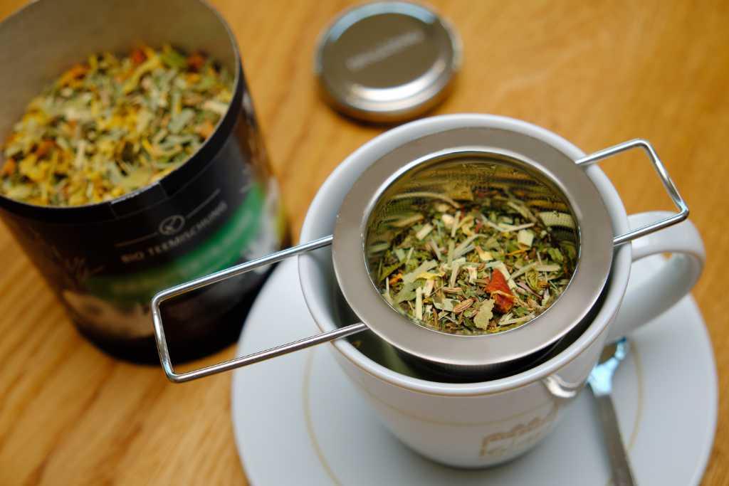 Eine Tasse wird mit losem Tee vorbereitet.