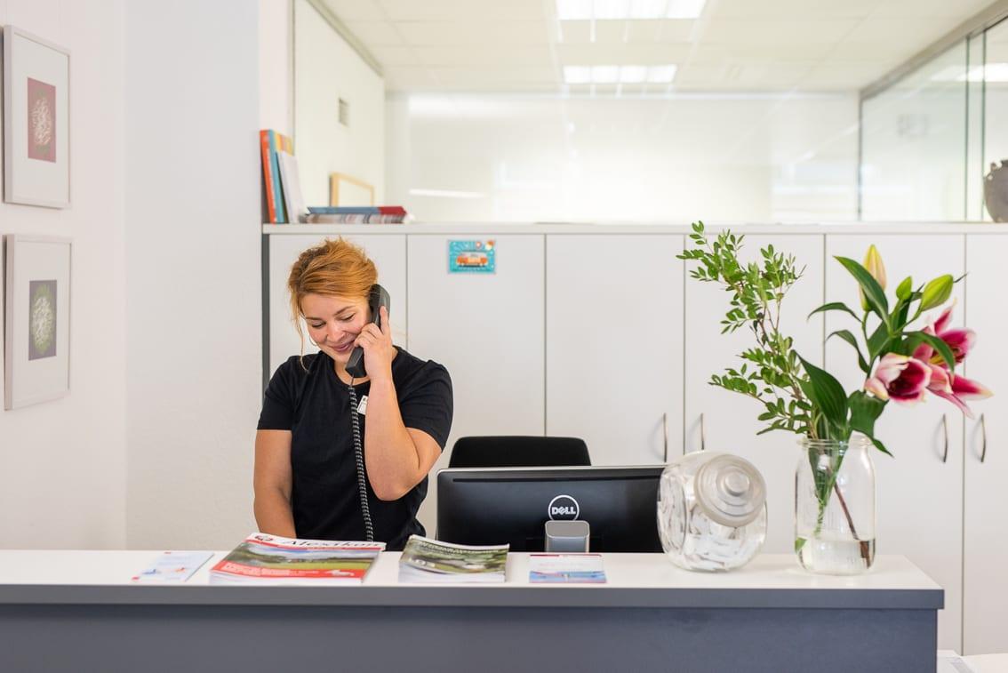 Eine Frau steht hinterm Schreibtisch und telefoniert.