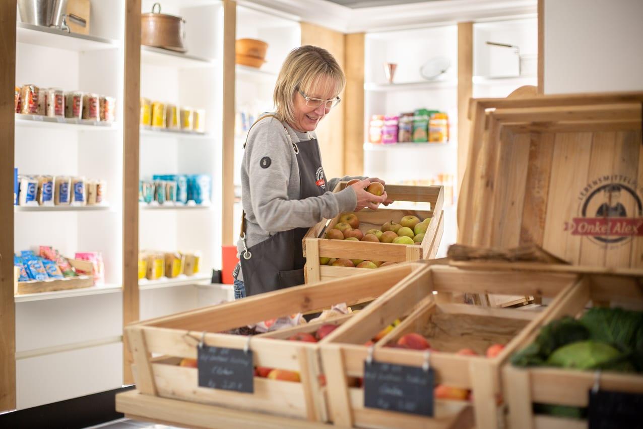 Eine Verkäuferin sortiert neue Äpfel in Holzkisten.