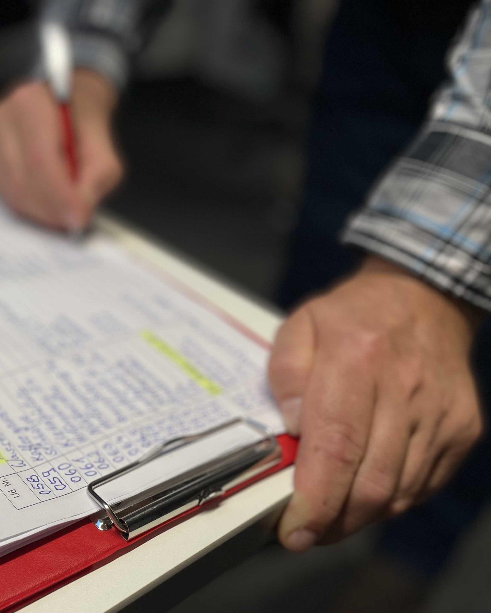 Jemand notiert Daten auf einem Blatt Papier.