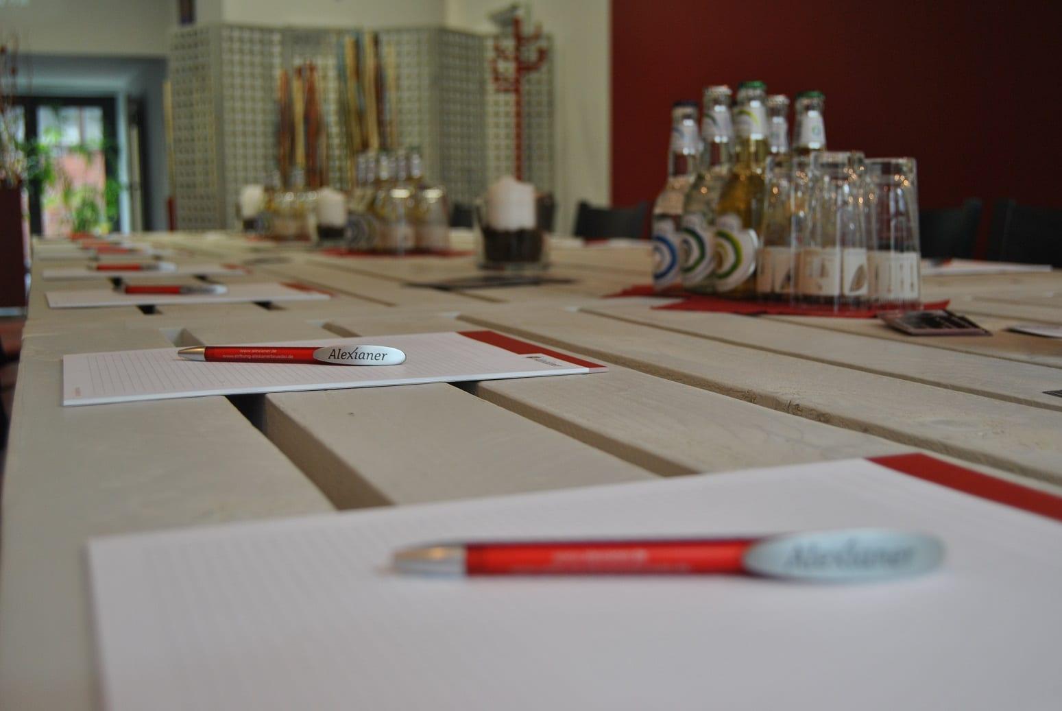 Papierblöcke und Stifte liegen auf einem Tisch.