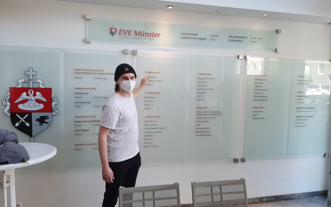 Ein Mitarbeiter der Werbetechnik steht vor der neuen Eingangstafel aus Glas im EVK Münster.
